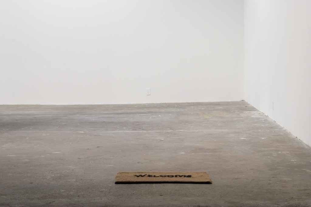 Frances Trombly, Welcome, 2006, Handwoven wool mat, 18 X 30 inches. Installation view at Locust Projects, Miami, FL